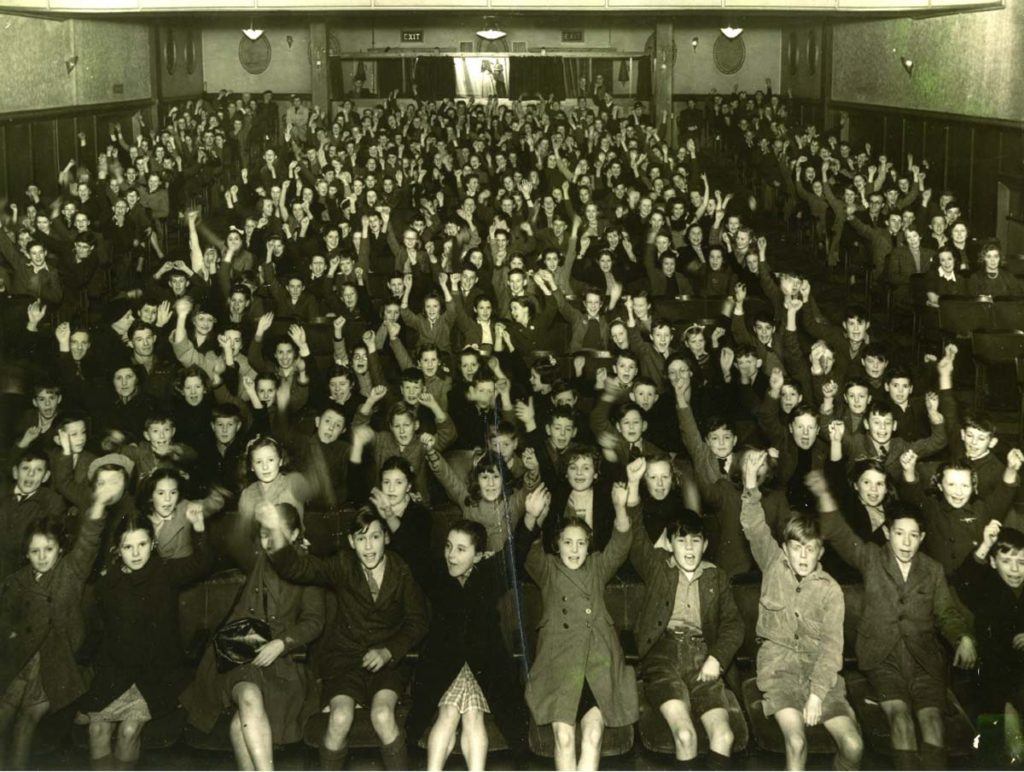 a photo of children cheering inside a packed cinema