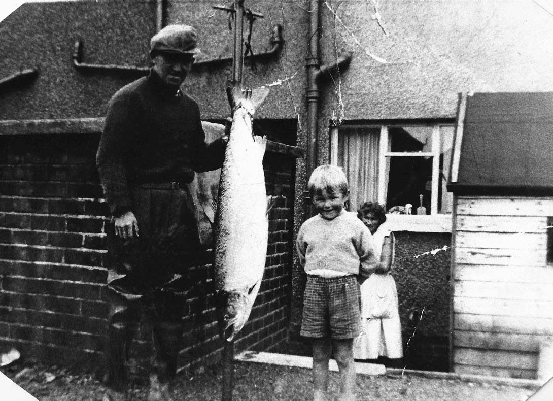 a black and white photo of a man holding a large fish next to small boy outside a house