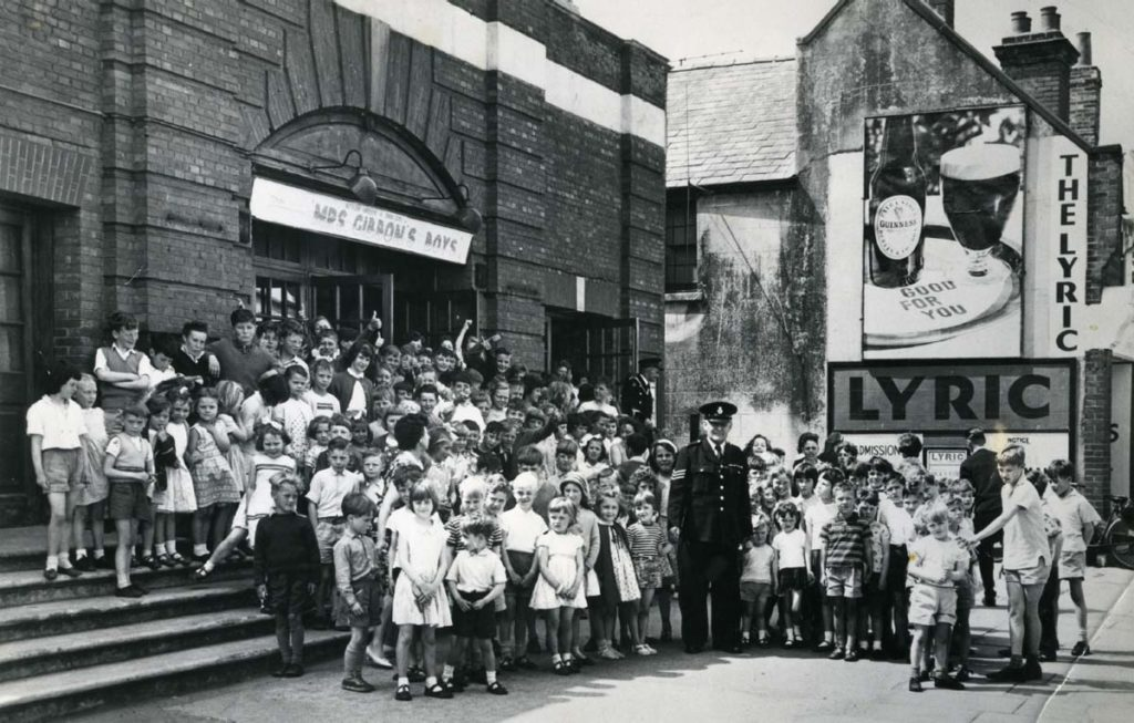 a black and white photo of children of all ages crowded outside a cinema