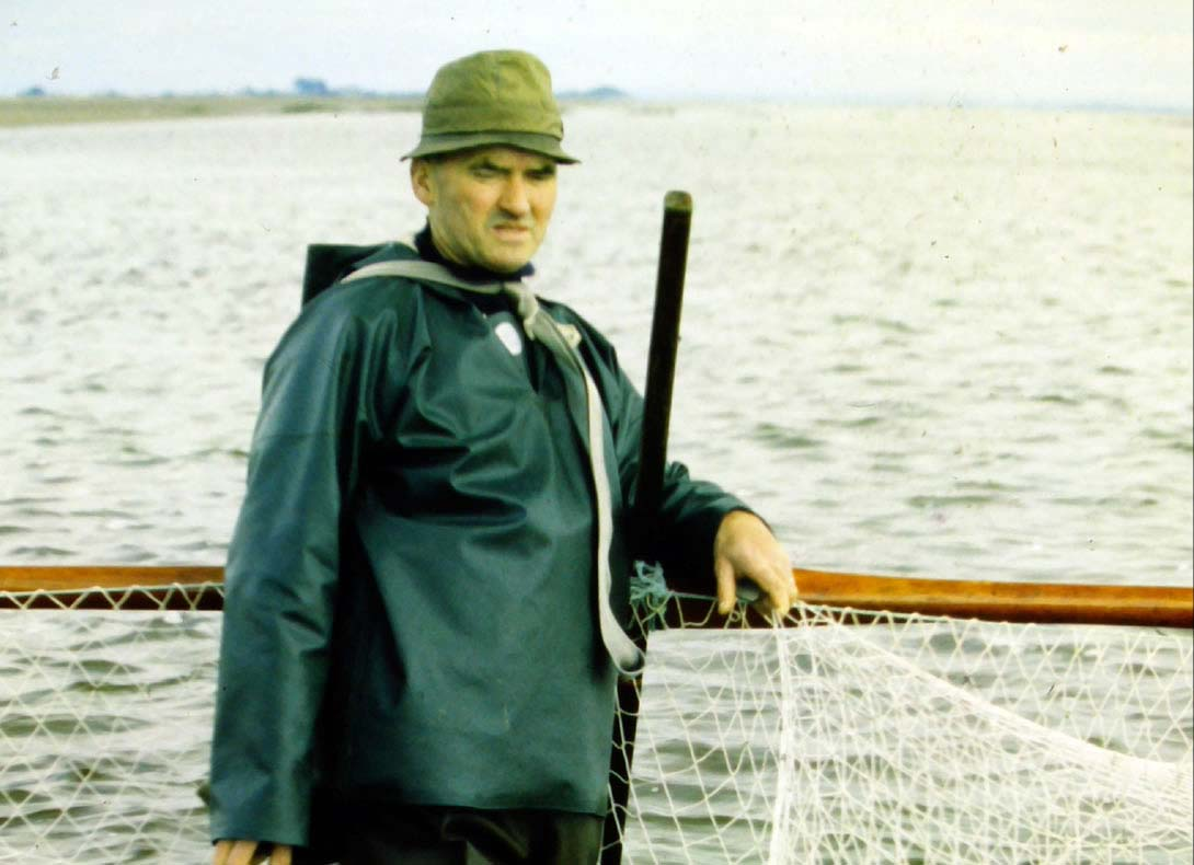a photo of a man standing in water holding net whilst wearing waterproofs and a tweed hat