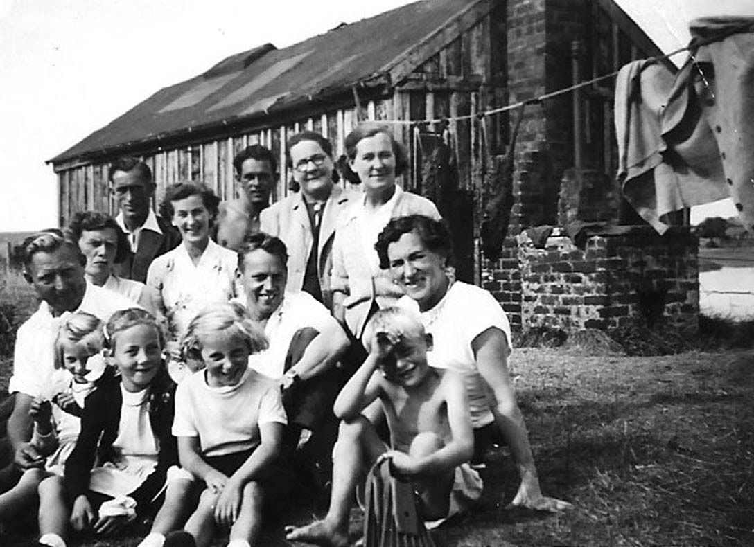 a photo of a family grouping of men women and children outside a hut with clothes drying on a washing line behind them