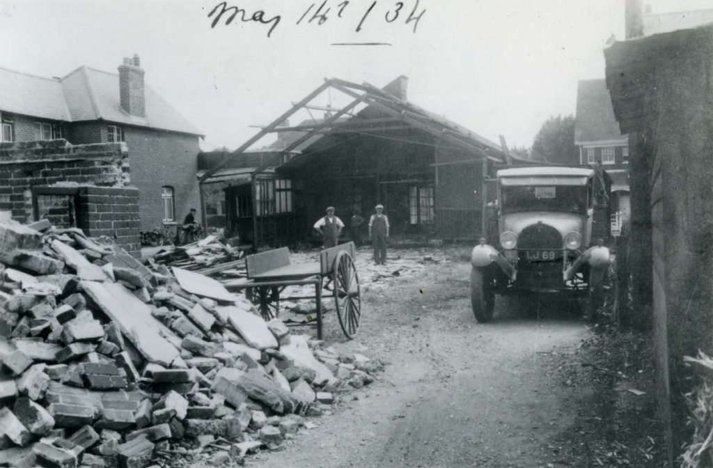 a photo of workmen next to a parially demolsihed apex roofed building