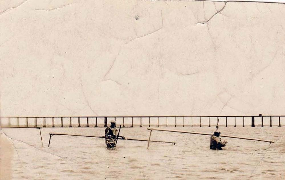 an old photo of two men wading across a river with large nets over their shoulders and a long viaduct in the background