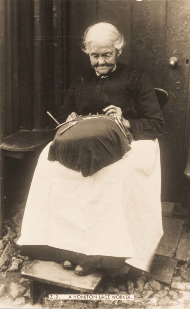 a photo of an elderyl woman seated making a lace decoration