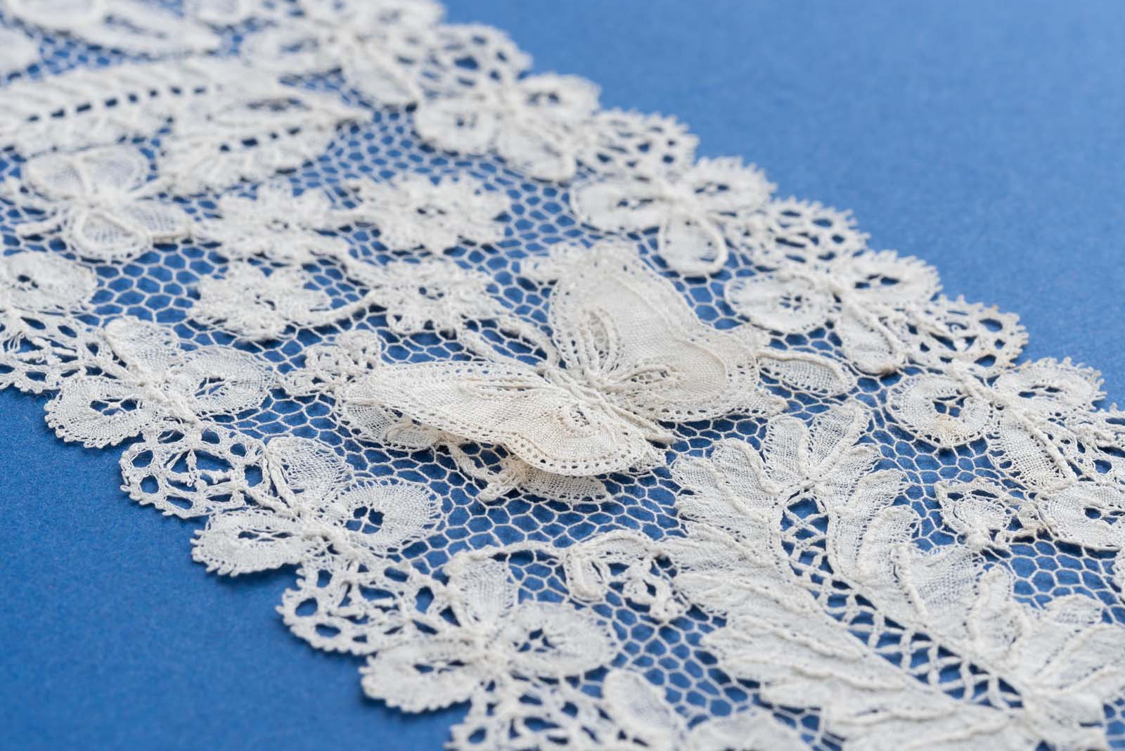 a close up photo of lace work with a butterfly decoration