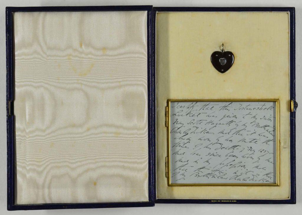 a heart shaped locket in a case with a handwritten inscription beneath it