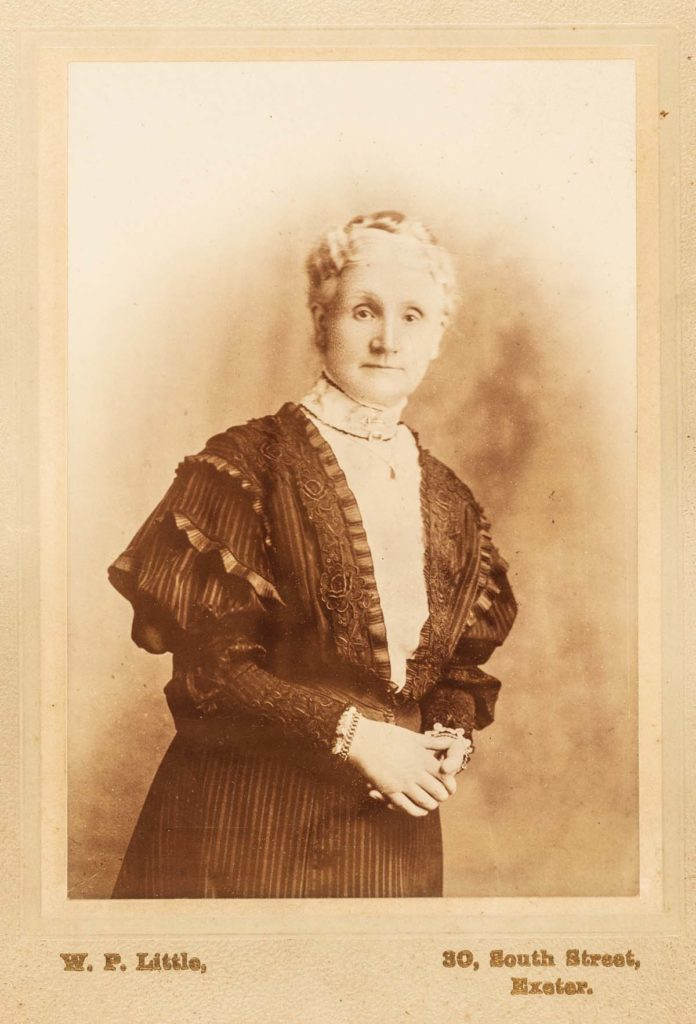 a sepia postcard photo of a woman in late Victorian dress