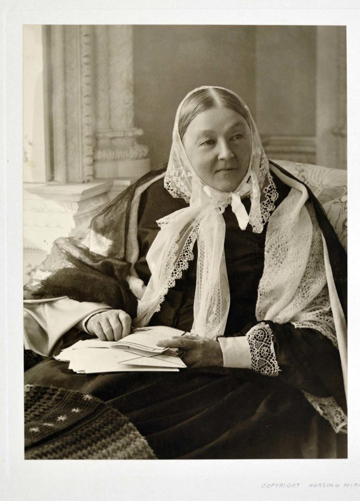 a photo of a woman in crocheted headscarf and dark clothes