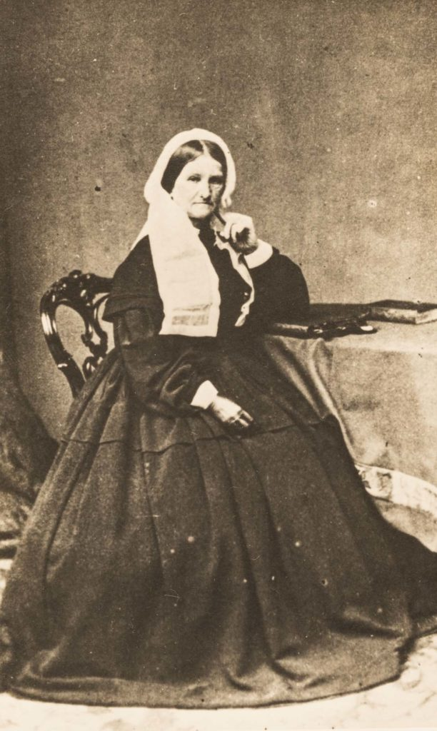 a photo of a woman in black Victorian clothes inlcuding a lace cap like Queen Victoria