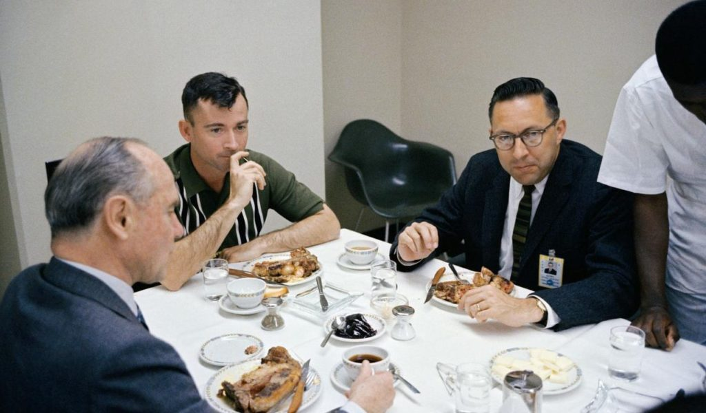 a photo of a young man with cre cut next older men with crew cuts eating food round a table