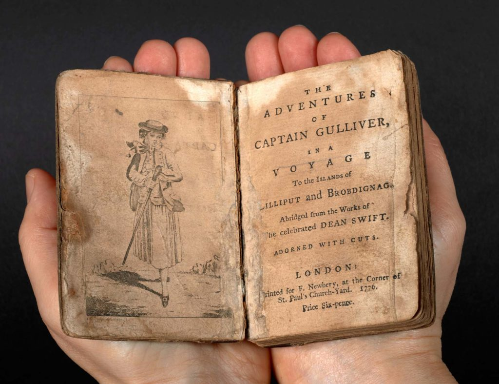 a photo of an open book held in two hands showing the frontispiece of Gulliver's Travels with illustration of Gulliver