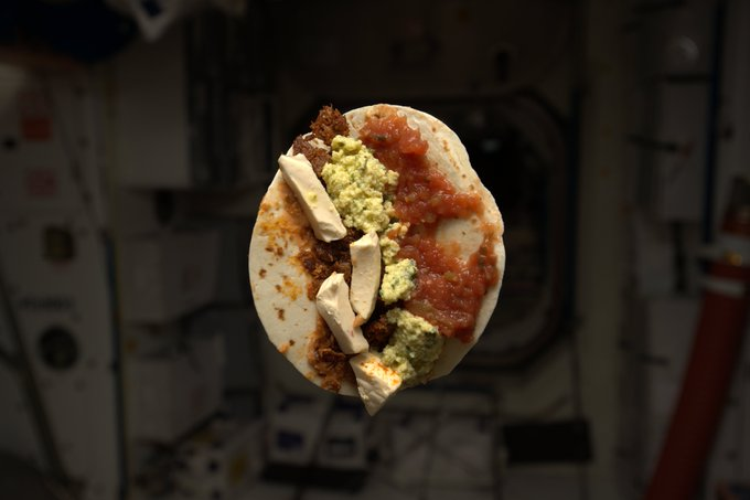 a photo of a taco covered in sauce and other foods floating in a capsule