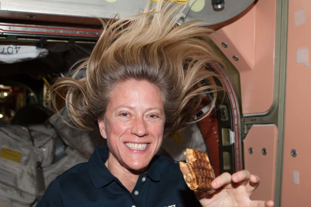 a photo of a female astronaut with her floating in the lack of gravity smiling as she holds a peanut butter and waffle sandwich