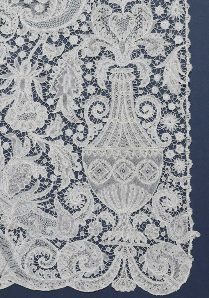 a detail of a piece of lace decoration with ornate vase and flower motifs