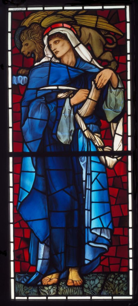 a stained glass window panel showing a saintly figure in a blue robe