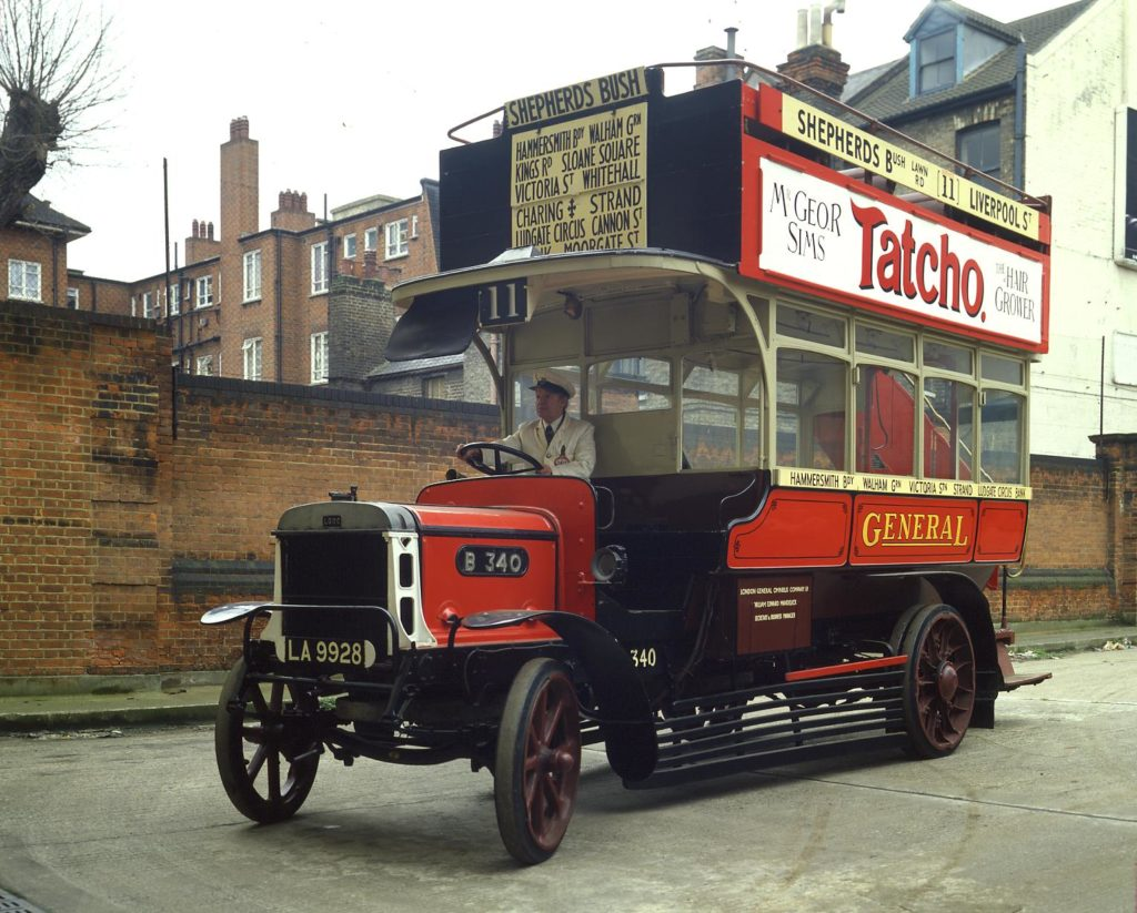 a photo of an old red open-topped bus