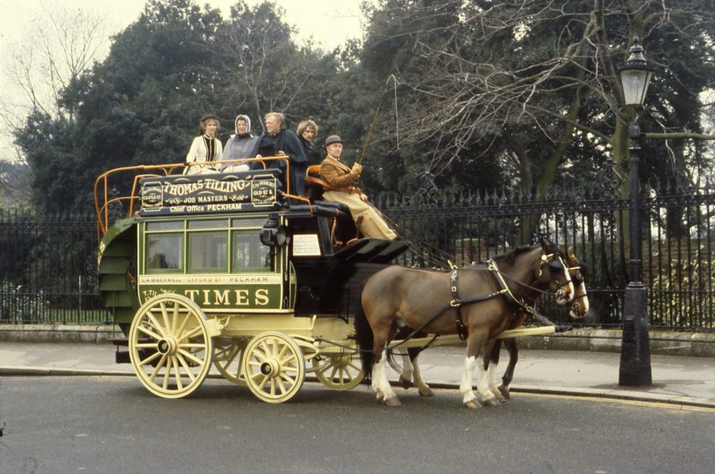 a photo of a bunch of a group of people on top of a horse drawn omnibus