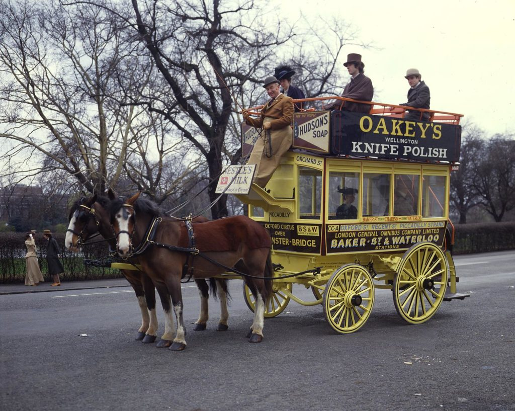 a photo of a group of people on top of a horse drawn omnibus