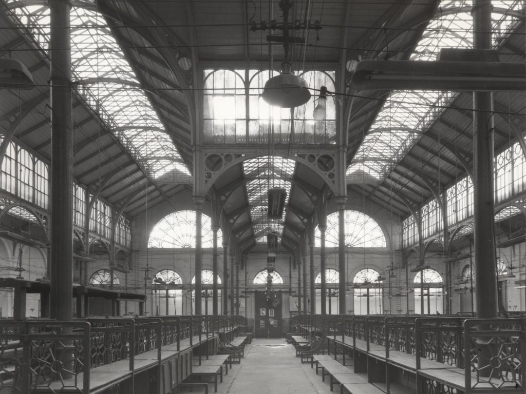 a black and white photo of a building with high glass ceiling
