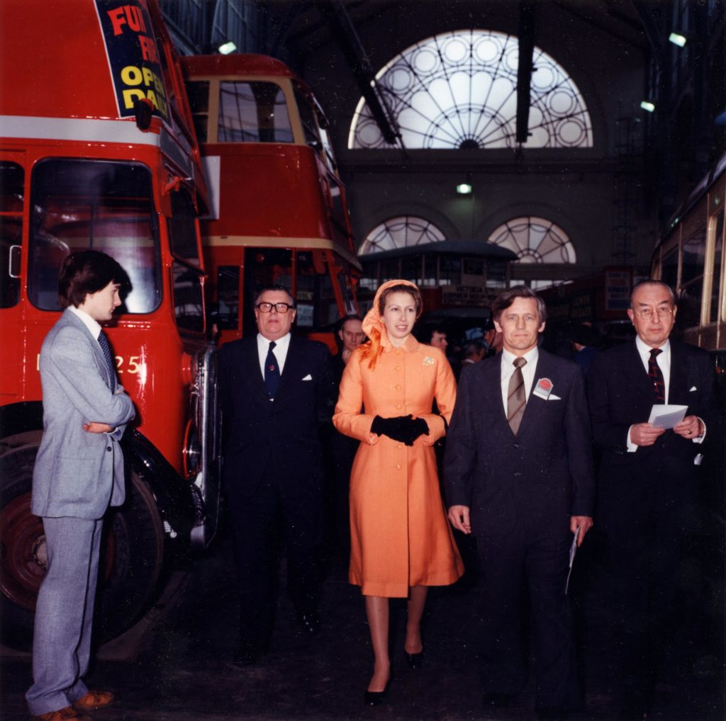 a photo of Princess Anne in a peach dress with several men in suits walking past a bus as another man in a suit stands by with his arms crossed self consciously