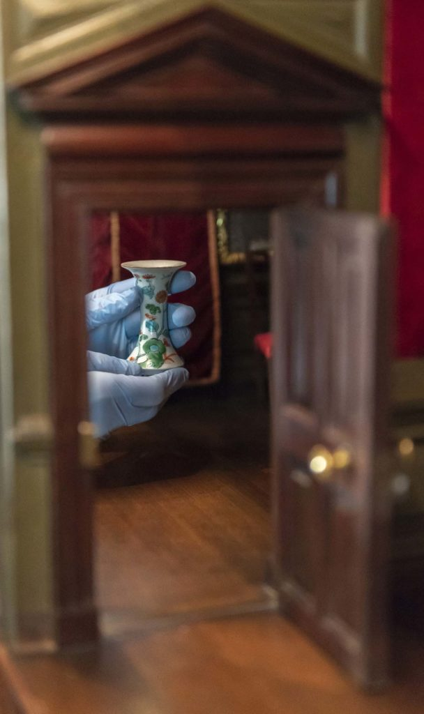 photo of a hand palcing a small vase inside a dolls house interior