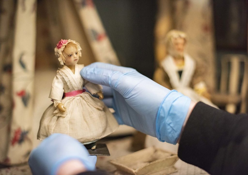 a photo of a pair of gloved curator hands holding a wax doll