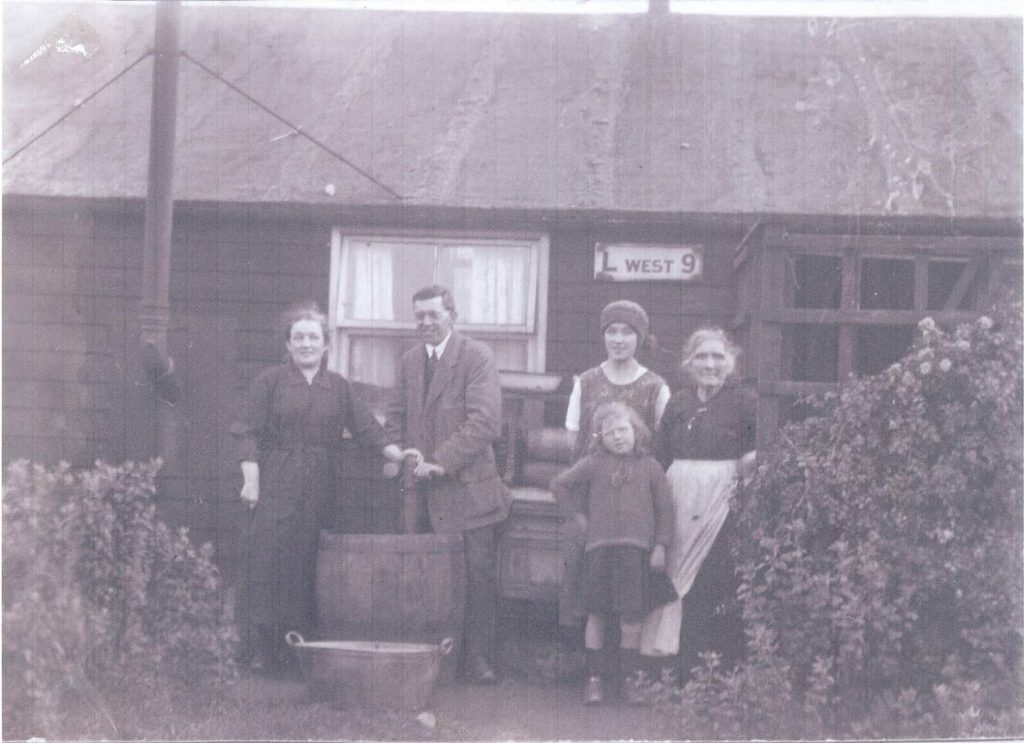 a black and white photo of women outside a wooden hut