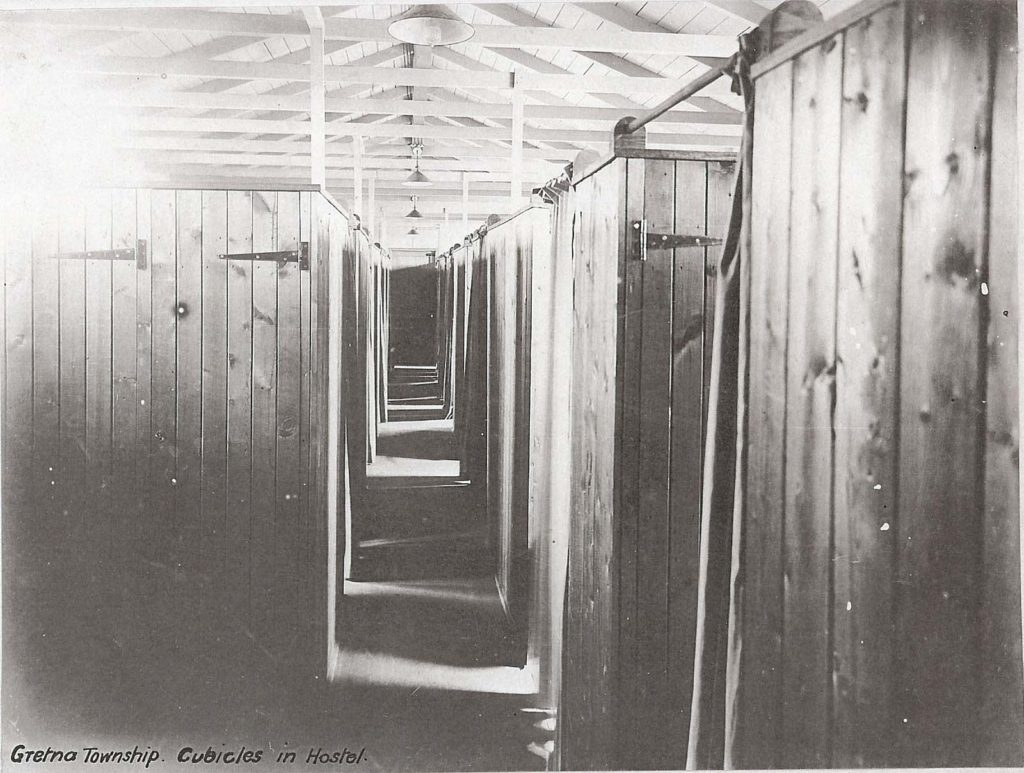 a black and white photo showing the interior cubicles of a wooden hostel