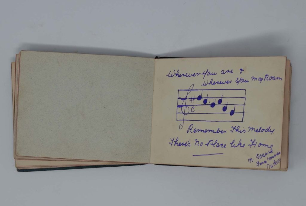 a photo of an open autograph book with a piece of handwritten music and words to there's no place like home