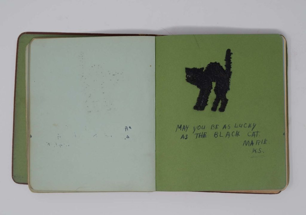 a photo of an autograph book with a drawing of a black cat inside it