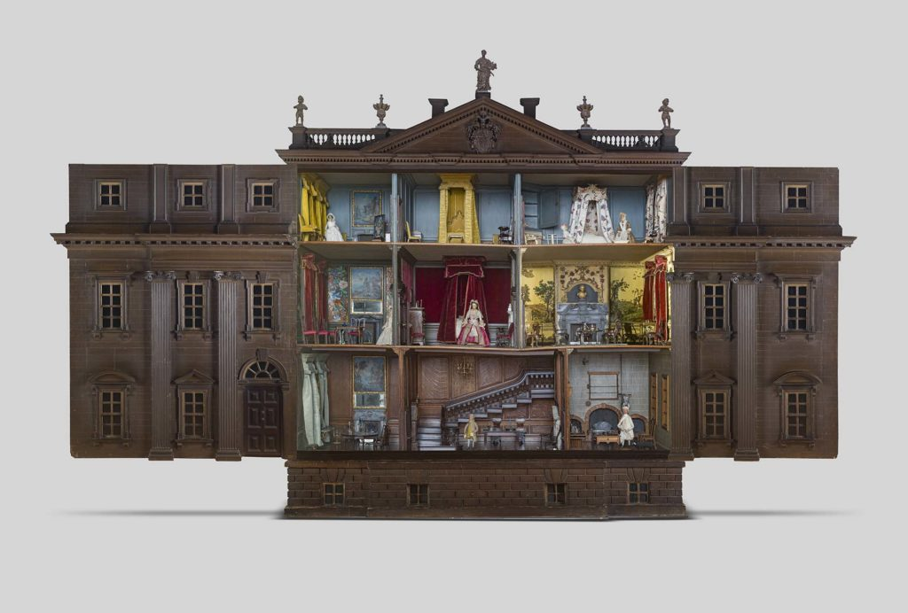 a photo of a large dolls house with its doors open showing the rooms inside