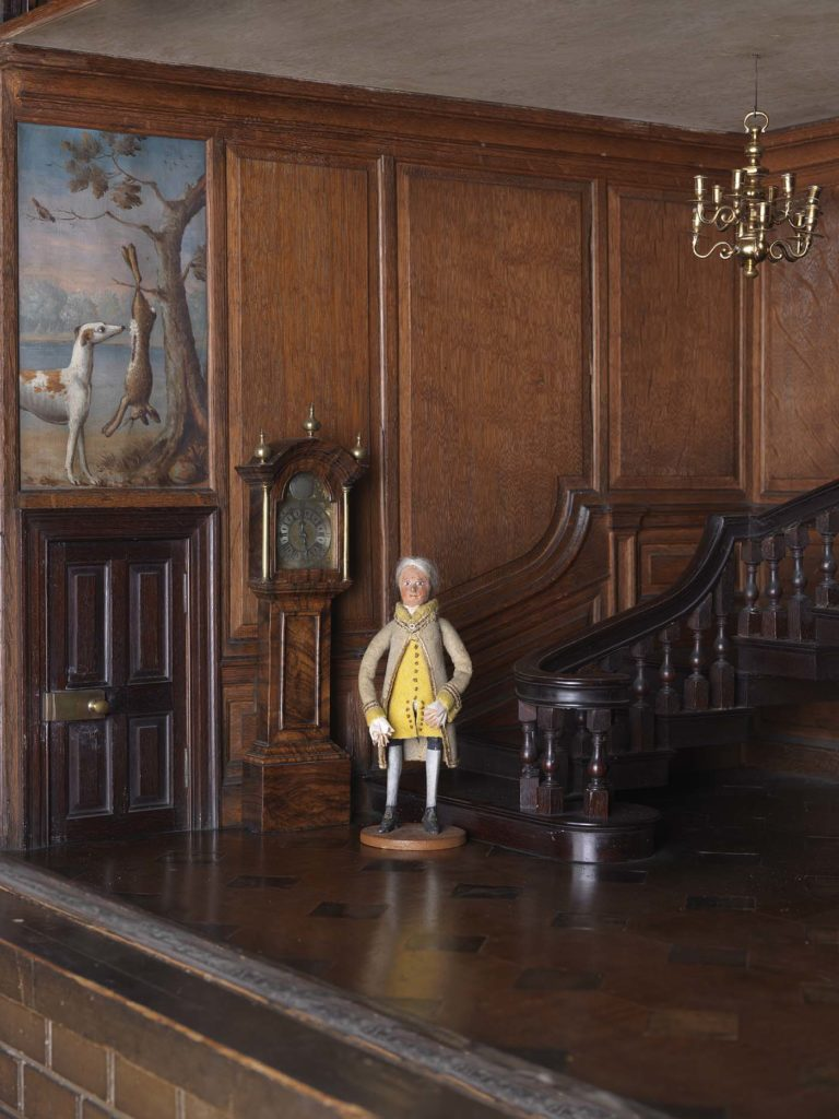 a photo of a wax doll dressed as a footman in a wooden hallway