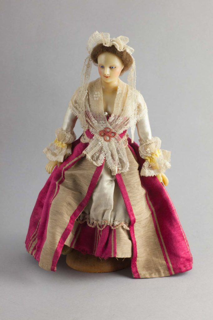a photo of a wax doll in ornate dress