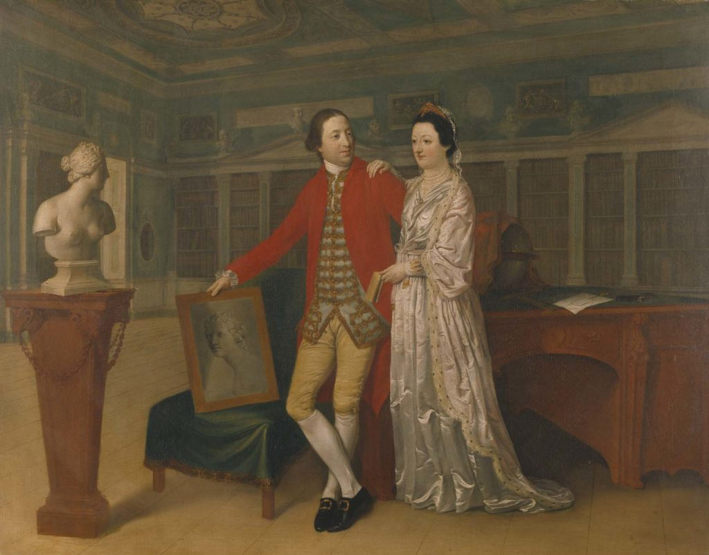 A double portrait of Sir Rowland and his wife whom he married in 1761, as a `conversation piece' and an allegory of art, standing in an idealised version of the Library at Nostell Priory. The bust of Venus, Roman Goddess of Love, on the pedestal and the chalk sketch of the same bust on the chair (whose features have been slightly altered to reflect Sabine's), symbolise the beauty of the 5th Baronet's wife and his love for her. Hamilton doubled the width of the Library to create a well proportioned composition. However, he accurately recorded its fittings and original decoration, as well as the famous Chippendale desk.