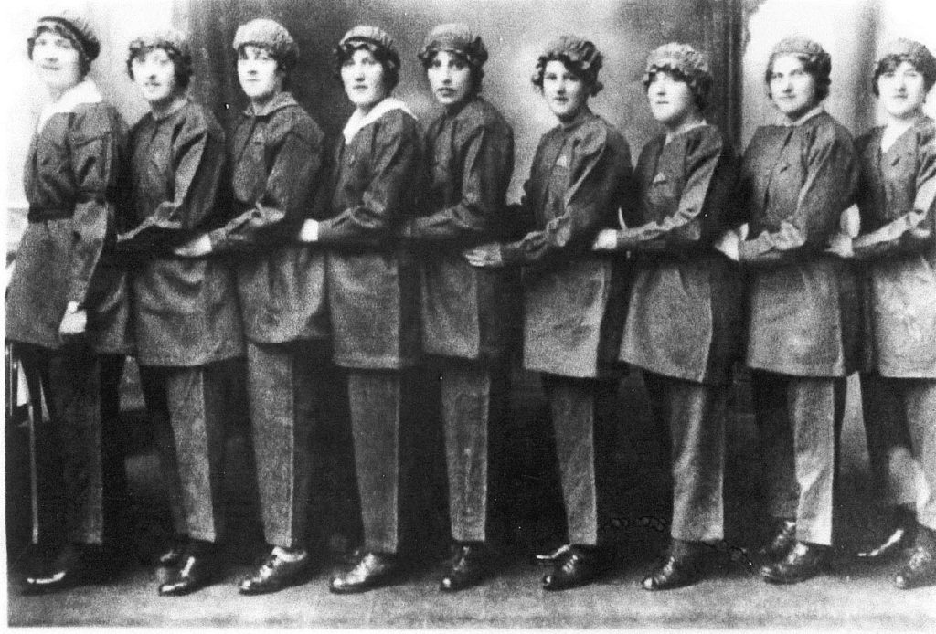 an old black and white photo of a group of munitions girls in a row