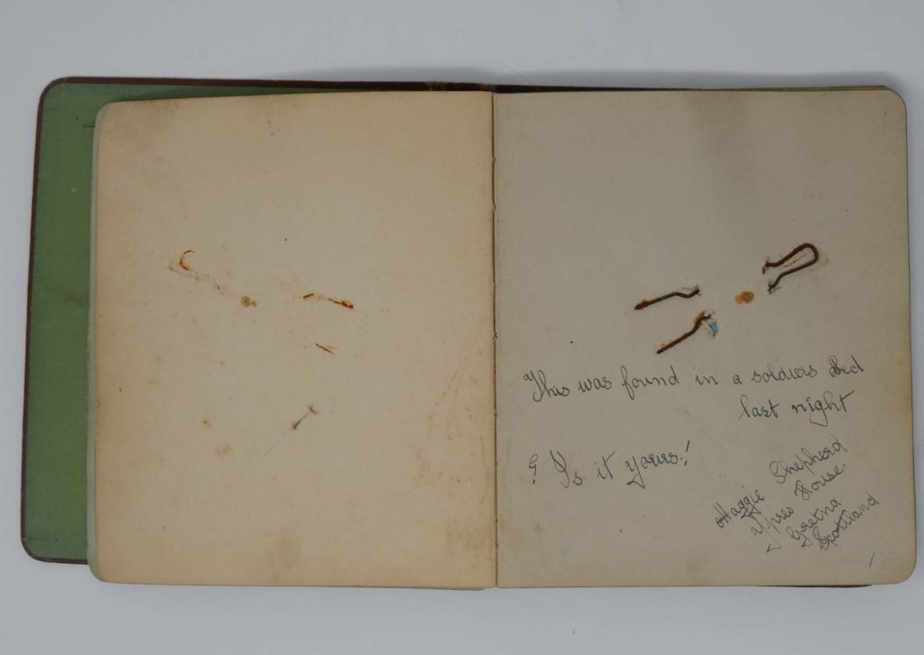 a photo of an open autograph book with an epigram and hairpin attached