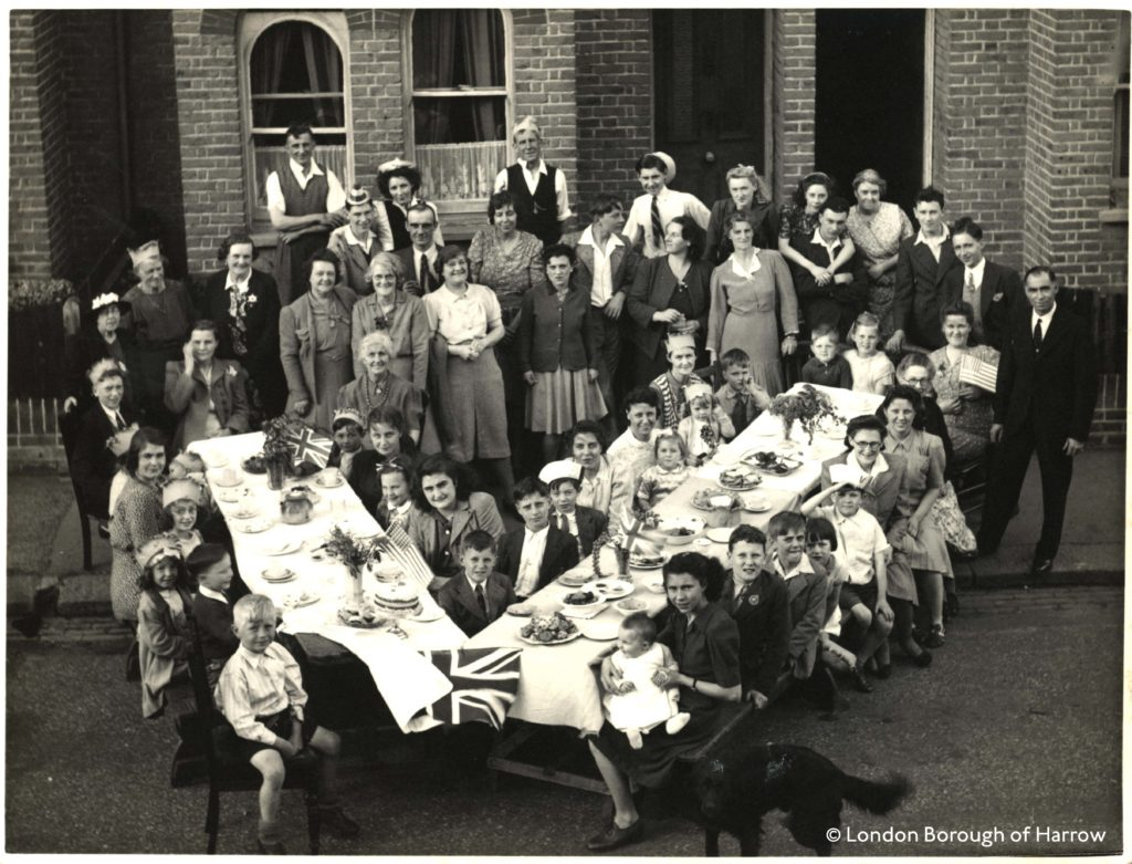 a photo of a group of people on a tressle tables arranged in the shape of a V