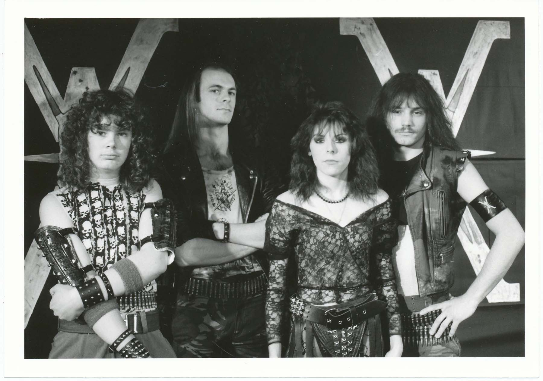 a photo of one woman and four blokes with long hair and leathers