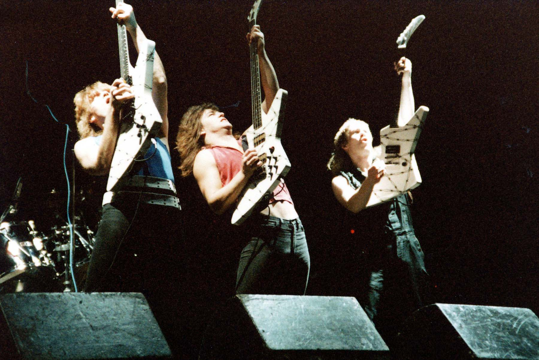 a photo of three heavy metal guitarists with their electric guitars raised in the air