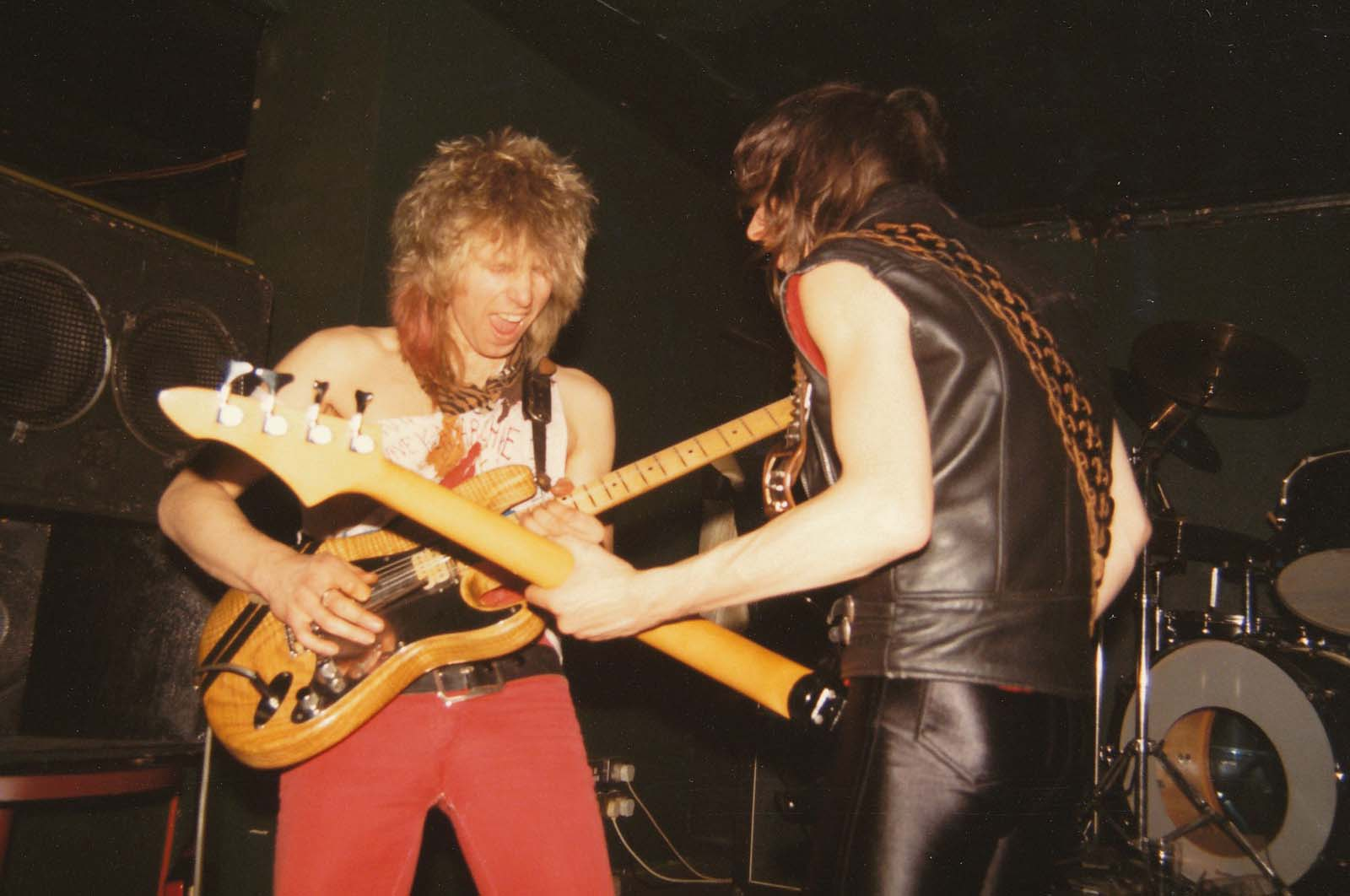 a photo of a two men with long haoir facing off with their electric guitars