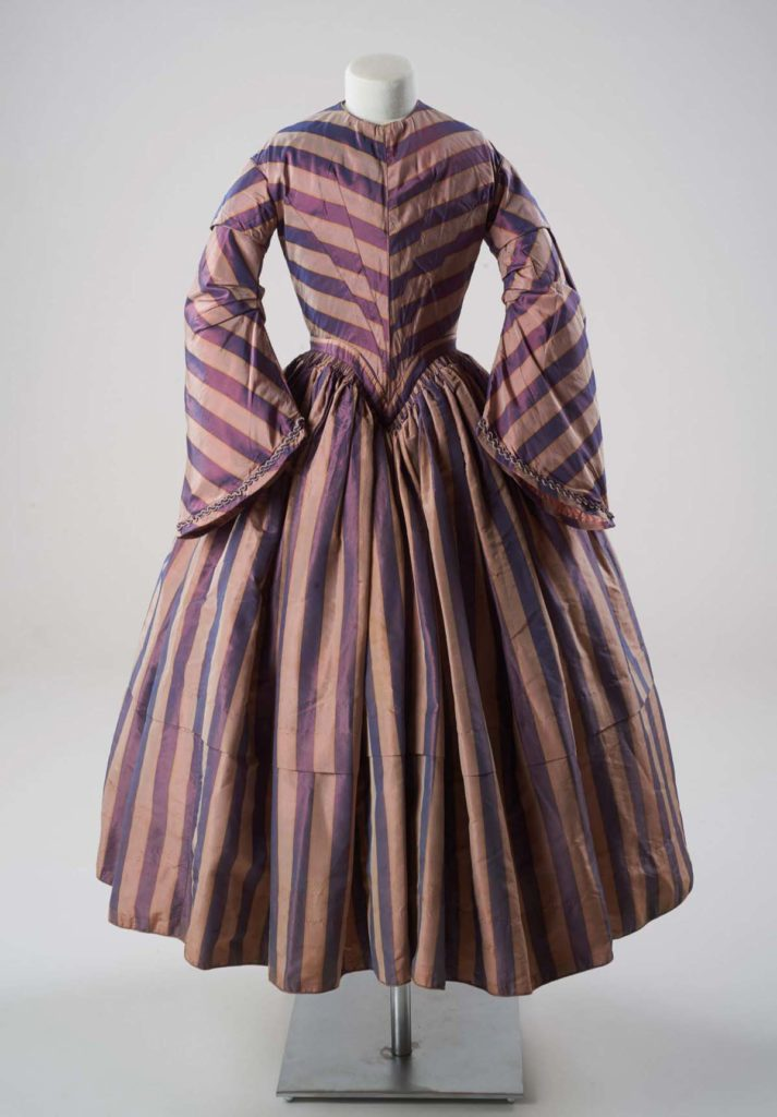 a bustle dress in pink and purple stripes with a long sleeves