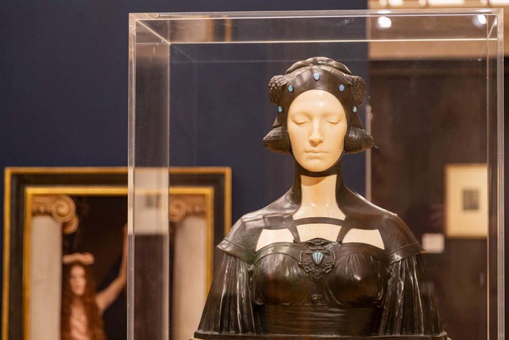 an exhibition display case showing a sculpture of a female in futuristic art deco dress