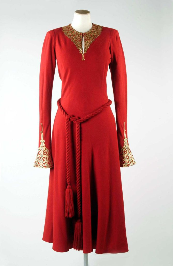 a red dress with robe tied belt and gold cuffs