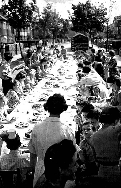 a black and white photo looking down a long table during a street party