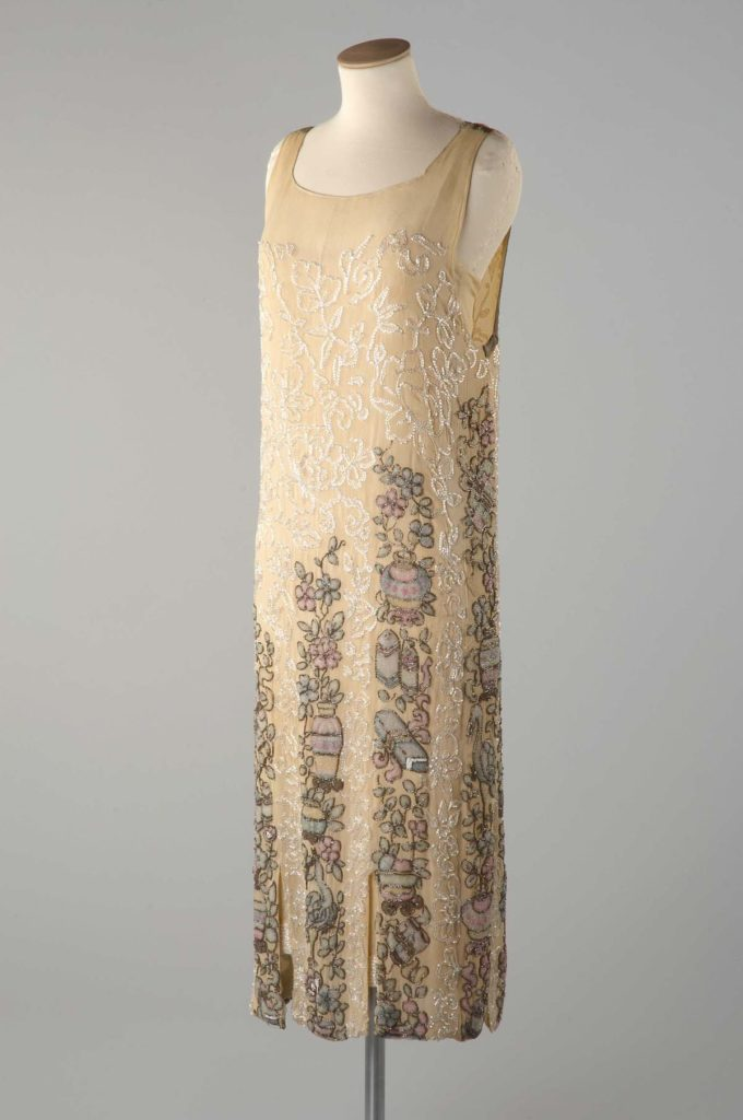 a slim 1920s style dress in cream silk and embroidery