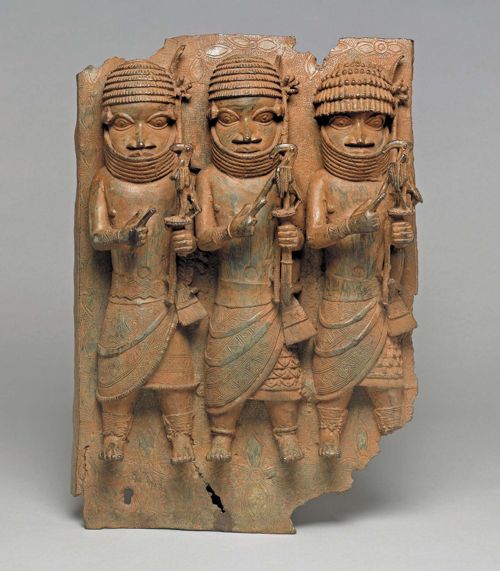 a relief sculpture in bronze showing three ceremonial figures with African style warrior costume
