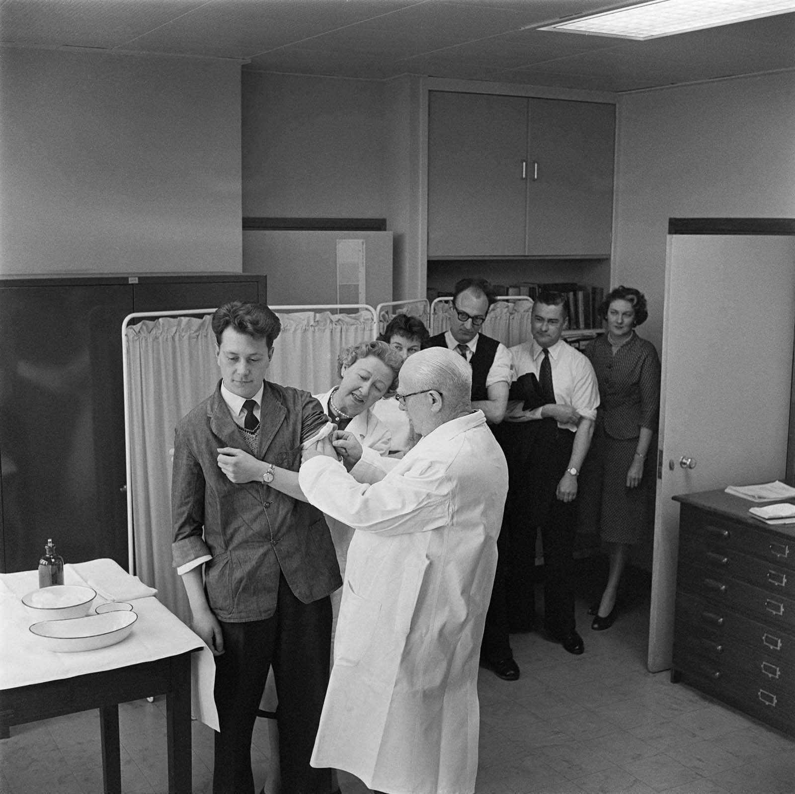 black and white photo of people waiting in line for an injection
