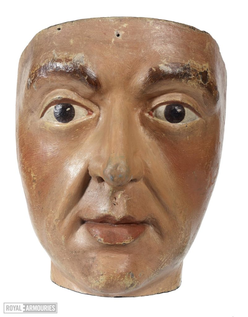 a head carved from wood and painted