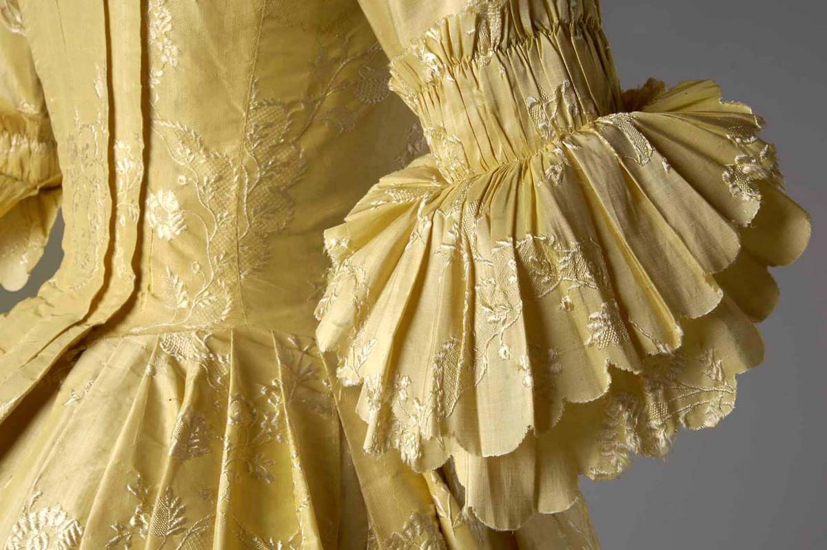 a close up of the ruffled sleeve of a golden brocaded lace gown