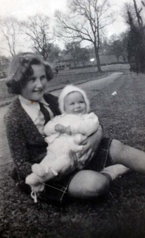 a black and white photo of young girl holding a baby in a park